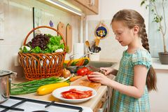 Child girl cooking in home kitchen, chopping tomatoes. Basket of vegetables and fresh fruits in kitchen interior. Healthy food con Royalty Free Stock Photography
