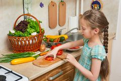 Child girl cooking in home kitchen, chopping tomatoes. Basket of vegetables and fresh fruits in kitchen interior. Healthy food con Royalty Free Stock Images