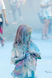Child girl covered with color dust, blue color dust in the backg Royalty Free Stock Image