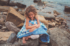 Child girl covered in quilt blanket, cozy summer holidays on seaside Royalty Free Stock Photography