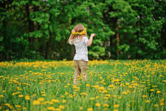 Child girl in dandelion wreath on spring flower field Stock Images