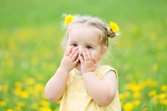 Child girl between dandelions Royalty Free Stock Image