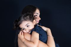 Child girl daughter hug in love mother arms shoulder in black background. A child girl daughter hug in love mother arms shoulder in black background royalty free stock photo