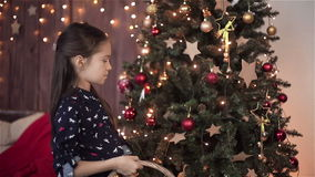 Child girl decorates the Christmas tree. HD shot with slider. stock footage