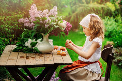 Child girl decorating cakes with flowers on garden tea party in spring Royalty Free Stock Image