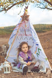 Child girl in decorative hovel on the nature Stock Photos