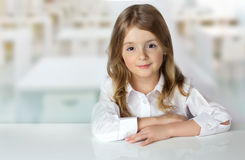 Child girl at desk in classroom background empty space. Royalty Free Stock Photo