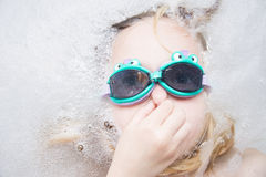 Child girl with diving goggles dive in the bathtub. Child girl with diving goggles dive in the bath with foam stock images