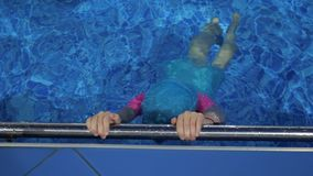 Child girl is diving underwater in swimming pool holding on the metal handrail. Small girl in swimming cap and swimsuit dives with breath holding in pool. Child stock video