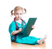 Child girl doctor writing to clipboard Royalty Free Stock Image