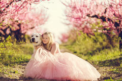 Child girl with dog in blooming garden Royalty Free Stock Photography