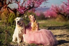 Child girl with dog in blooming garden Stock Photos