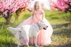 Child girl with dog in blooming garden Stock Images