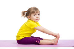 Child girl doing gymnastic exercises. Child girl doing fitness exercises on gymnastic mat Royalty Free Stock Photos