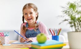 Child  girl  doing homework writing and reading at home Stock Photo