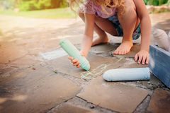 Child girl drawing with chalks in summer Stock Images