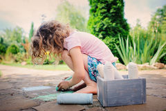 Child girl drawing with chalks in summer Royalty Free Stock Photos