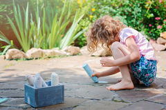 Child girl drawing with chalks in summer Stock Image