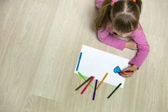 Child girl drawing with colorful pencils crayons heart on white paper. Art education, creativity concept.  stock images