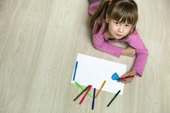 Child girl drawing with colorful pencils crayons heart on white paper. Art education, creativity concept.  royalty free stock photo
