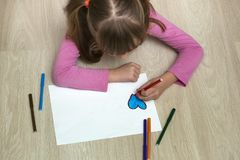 Child girl drawing with colorful pencils crayons heart on white paper. Art education, creativity concept.  royalty free stock image