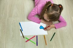 Child girl drawing with colorful pencils crayons heart on white paper. Art education, creativity concept royalty free stock images