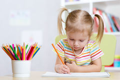 Child girl drawing with colorful pencils in nursery Royalty Free Stock Photos