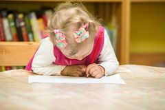 Child girl drawing with colorful pencils in preschool at the table. Little girl drawing in kindergarten Stock Photos