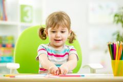 Child girl drawing with colourful pencils Royalty Free Stock Images