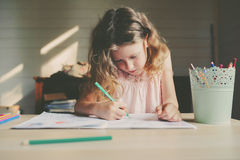 Child girl drawing at home with pencils. Child girl drawing at home with colored pencils royalty free stock photo
