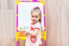 Child girl drawing on white board. Little child girl drawing on white board stock image