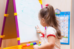 Child girl drawing on white board. Little child girl drawing on white board Royalty Free Stock Images
