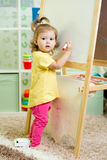 Child girl draws on white board. Child girl drawing on white board Stock Photography