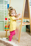 Child girl draws on white board Stock Photos