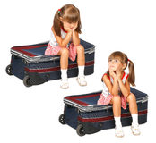 Child girl dreaming. And longing, sitting on a suitcase Royalty Free Stock Image