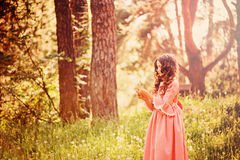 Child girl dressed as fairytale princess playing with blow ball in summer forest Royalty Free Stock Photo