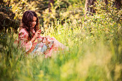 Child girl dressed as fairytale princess playing with doll in summer forest Stock Photos