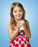 Child girl drink hold glass milk isolated on blue background. Child girl hold glass milk isolated on blue background. Kid female in red dress drinking,healthy Royalty Free Stock Image