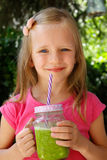 Child girl drinking healthy green vegetable smoothie - healthy eating, vegan, vegetarian, organic food and drink concept Stock Photo