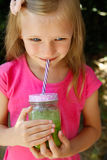 Child girl drinking healthy green vegetable smoothie - healthy eating, vegan, vegetarian, organic food and drink concept Stock Photos