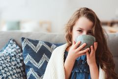 Child girl drinking hot tea to recover from flu. Healing kids and protect immunity from seasonal virus, health concept Stock Images