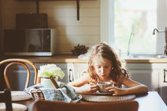 Child girl drinking tea for breakfast in summer country kitchen Stock Image