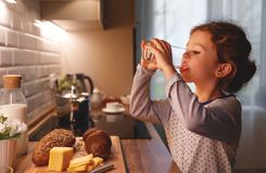 Child girl is drinking water in  kitchen at home Stock Photos
