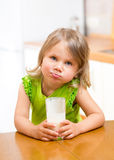 Child girl drinking yogurt or milk in kitchen. Child drinking yogurt or milk in kitchen stock image