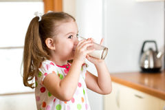 Child girl drinking yogurt or milk in kitchen Stock Photo