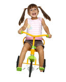 Child girl drive bicycle. Child girl with long tails drive bicycle very fast Royalty Free Stock Images