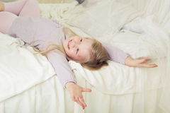 Child girl at early morning lying in bed Stock Images