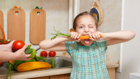 Child girl eat carrot, vegetables and fresh fruits in kitchen interior, healthy food concept Stock Photo