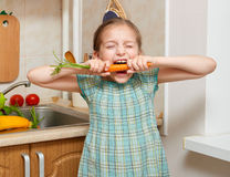 Child girl eat carrot, vegetables and fresh fruits in kitchen interior, healthy food concept stock image