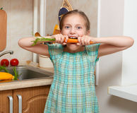 Child girl eat carrot, vegetables and fresh fruits in kitchen interior, healthy food concept Stock Photography